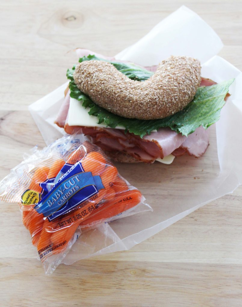 Healthy Bagel Sandwich to go wrapped in wax paper with a side of baby carrots