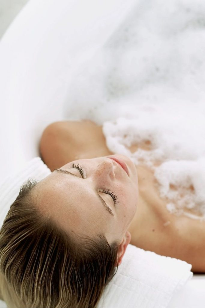 Self Care for Fitness - Soak- woman soaking sore muscles in a warm bath