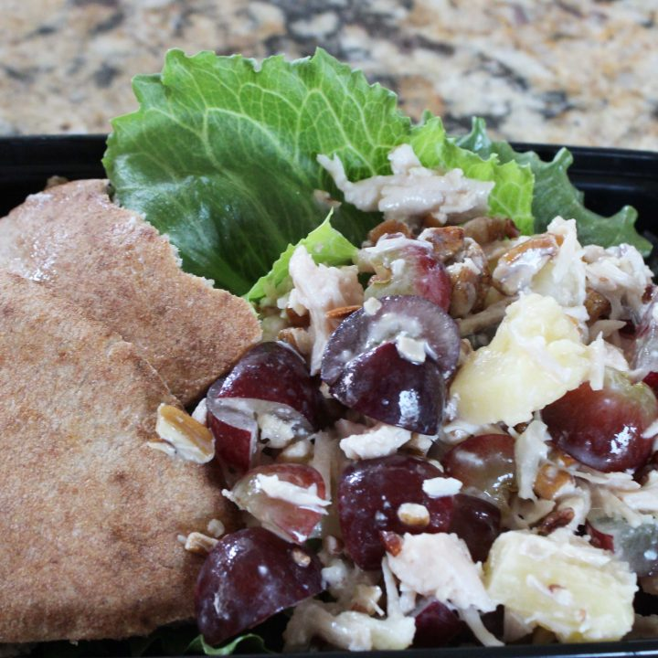 easy chicken salad shown meal prepped with lettuce and pita bread